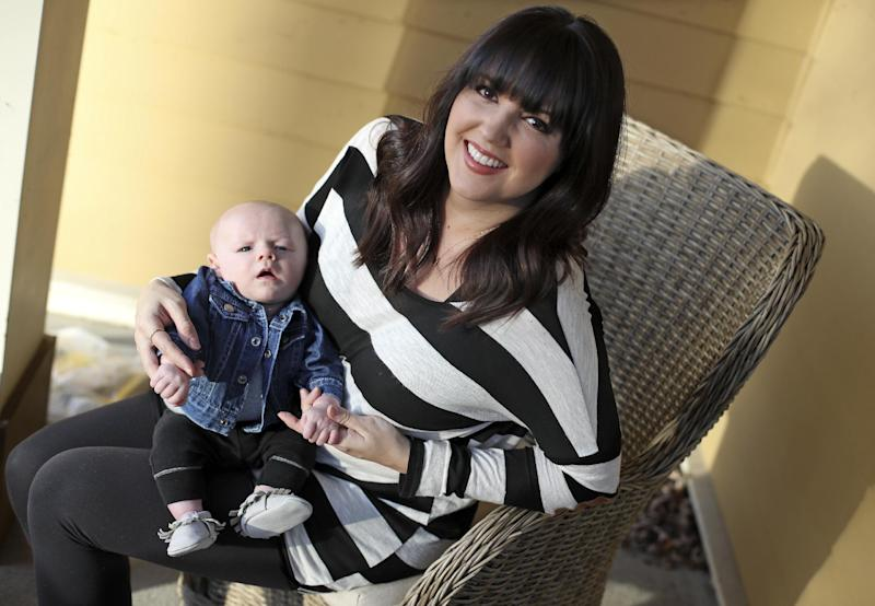 """Rachel Potter holds her son, Jude, Tuesday, Jan. 31, 2017, at their home in Nashville, Tenn. Potter, a Nashville-based singer who has toured the country as part of the cast of the hit musical """"Wicked"""" as well as performing gigs with her country music band Steel Union, said she couldn't afford insurance before the Affordable Care Act. From a return to higher premiums based on female gender, to gaps in coverage for breast pumps used by nursing mothers, President Donald Trump's vow to repeal his predecessor's health care law is raising concerns about the impact on women's health. (AP Photo/Mark Humphrey)"""