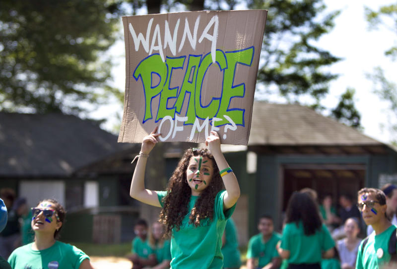 A camper cheers during a softball game at the Seeds of Peace camp in Otisfield, Maine, Friday, July 5, 2013. The summer camp brings together young people from countries at conflict. (AP Photo/Robert F. Bukaty)