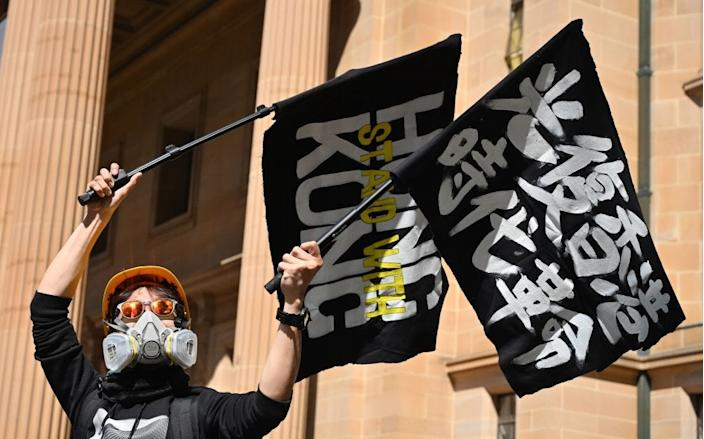 "A supporter of the Hong Kong pro-democracy protesters waves flags during a demonstration as part of the global ""anti-totalitarianism"" movement in Sydney on September 29, 2019."