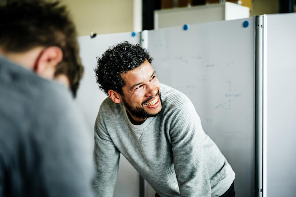 Portrait of a casual afro-american businessman during a  meeting. He's smiling to his colleague