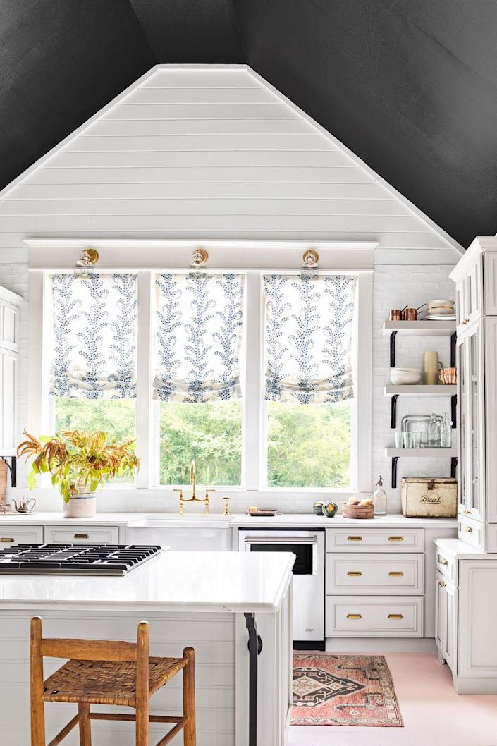 """<p>Choose contrasting ceiling and wall colors to highlight architectural details, like the pitch in this large, open kitchen. Brackets on the open shelving and island pick up the black hue from the ceiling, while ballet-slipper pink floors add an unexpected and happy element to the crisp white cook space in this <a href=""""https://www.countryliving.com/remodeling-renovation/home-makeovers/g3316/2016-makeover-takeover-holly-williams/"""" rel=""""nofollow noopener"""" target=""""_blank"""" data-ylk=""""slk:Tennessee home"""" class=""""link rapid-noclick-resp"""">Tennessee home</a>.</p>"""