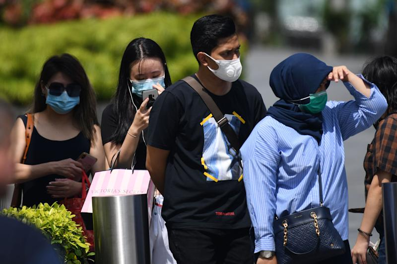 People wearing protective facemasks wait at a pedestrian crossing in Singapore on February 4, 2020. - Singapore has 18 cases of individuals infected with the novel coronavirus, which originated from Wuhan in China late last year. (Photo by Roslan RAHMAN / AFP) (Photo by ROSLAN RAHMAN/AFP via Getty Images)