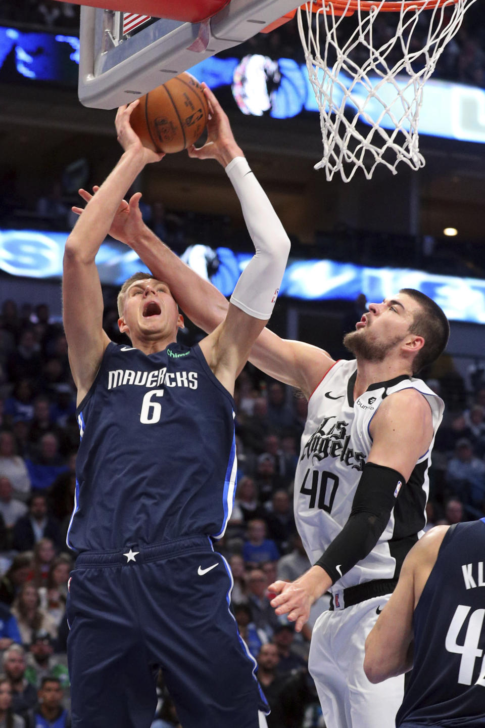 Dallas Mavericks forward Kristaps Porzingis (6) gets fouled as he goes up for a shot against Los Angeles Clippers center Ivica Zubac (40) during the first half of an NBA basketball game Tuesday, Jan. 21, 2020 in Dallas. (AP Photo/Richard W. Rodriguez)