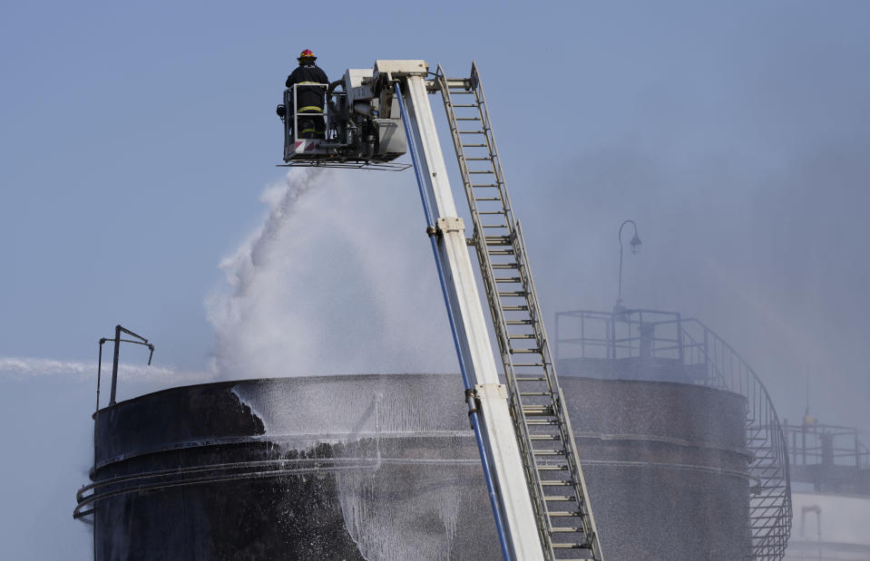 A firefighter works to extinguish a fire at an oil facility in the southern town of Zahrani, south of the port city of Sidon, Lebanon, Monday, Oct. 11, 2021. Firefighters extinguished the huge blaze that broke out in a storage tank at one of Lebanon's main oil facilities in the country's south Monday after it sent orange flames and a thick black column of smoke into the sky. (AP Photo/Hassan Ammar)