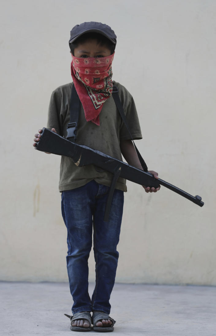 A child holds a fake, wooden rifle during a display for the media designed to attract the federal government's attention to the dangers of organized crime his town negotiates daily in Ayahualtempa, Guerrero state, Mexico, Wednesday, April 28, 2021. Residents' demands included more National Guard troops and help for orphans, widows and those displaced by violence that has cost 34 lives in various communities of two neighboring municipalities in the past two years. (AP Photo/Marco Ugarte)