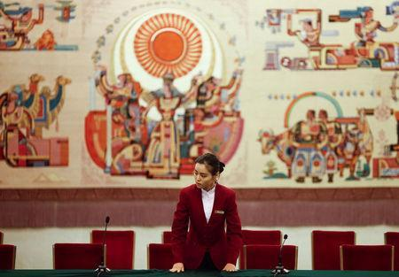 An attendant prepares a table for a session on the second day of the 19th National Congress of the Communist Party of China at the Great Hall of the People in Beijing, October 19, 2017. REUTERS/Thomas Peter