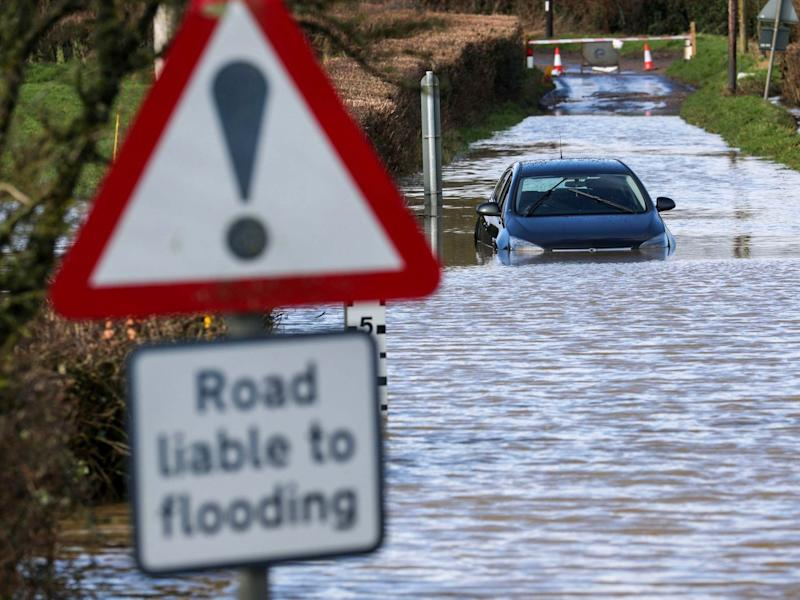 A car is stuck in flood water near Peasmarsh, Somerset, on Thursday February 13, 2020: PA