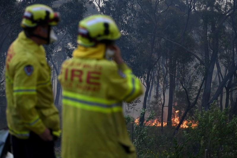 NSW Rural Fire Service and Fire and Rescue NSW personnel conduct property protection as a bushfire burns in Woodford NSW