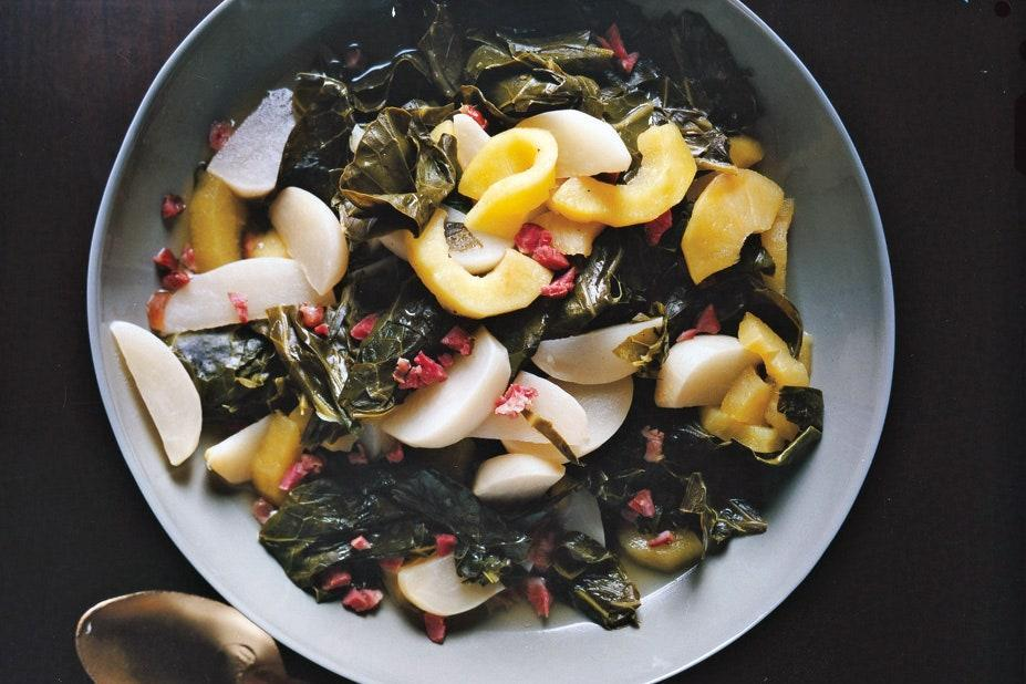 """Turnip greens, braised gently with a smoked ham hock, are a time-honored accompaniment on southern tables at any time of the year. This version is extra-pretty, with the ivory turnips, golden apple, and pink ham nestled among the dark greens. <a href=""""https://www.epicurious.com/recipes/food/views/braised-turnip-greens-with-turnips-and-apples-356069?mbid=synd_yahoo_rss"""" rel=""""nofollow noopener"""" target=""""_blank"""" data-ylk=""""slk:See recipe."""" class=""""link rapid-noclick-resp"""">See recipe.</a>"""