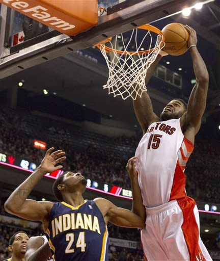 Toronto Raptors' Amir Johnson (15) scores as Indiana Pacers' Paul George (24) looks on during first half NBA basketball action in Toronto, Friday, Jan. 13, 2012. (AP Photo/The Canadian Press, Chris Young)