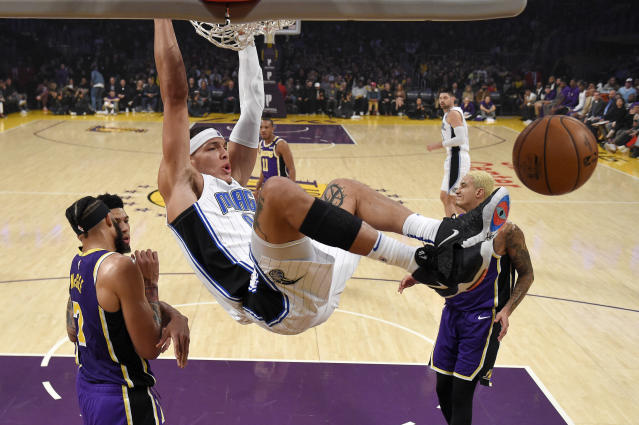 Orlando Magic forward Aaron Gordon, center, dunks as Los Angeles Lakers center JaVale McGee, left, and forward Kyle Kuzma, right, stand by during the first half of an NBA basketball game Wednesday, Jan. 15, 2020, in Los Angeles. (AP Photo/Mark J. Terrill)