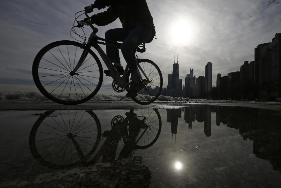 A cyclist is reflected in a puddle as he rides along the beach in Chicago, Illinois, January 13, 2014. After a blast of Arctic air gripped the vast middle of the United States last week, bringing the coldest temperatures in two decades, above freezing temperatures rolled into the city to melt the snow and ice. REUTERS/Jim Young  (UNITED STATES - Tags: ENVIRONMENT SOCIETY)