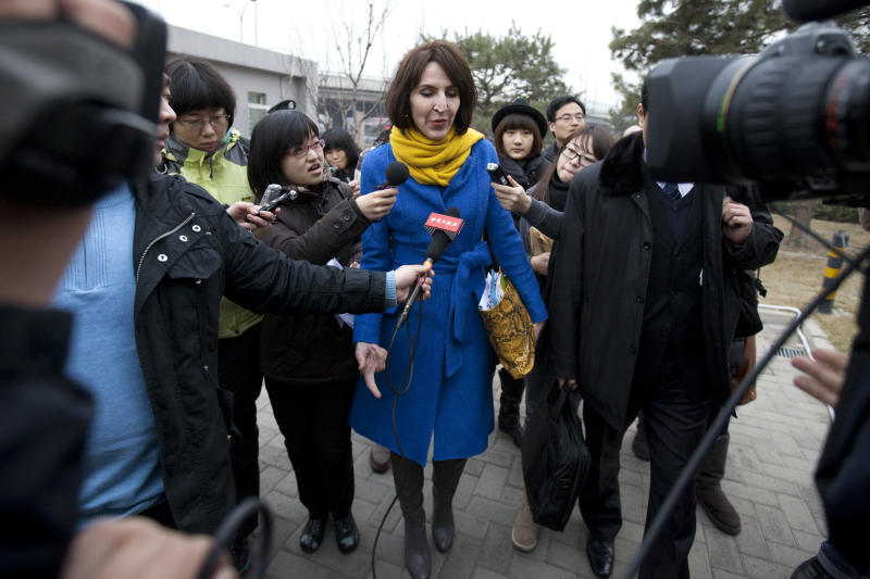 "In this Thursday, March 22, 2012 photo, Kim Lee, center, wife of ""Crazy English"" founder Li Yang, is surrounded by local journalists as she walks into a court for her divorce trial in Beijing, China. Lee's case has opened the door to a torrent of anguish about domestic violence in her adopted country, and she has became a folk hero for battered Chinese women. In China, where tradition holds that family matters are private and women are in many ways subservient to their husbands, the American woman's case has spawned tens of thousands of postings on Twitter-like sites, along with protests and talk show debates. It is especially explosive because she is a foreigner, at a time when China is particularly sensitive about how it is understood and treated by the world. (AP Photo/Alexander F. Yuan)"