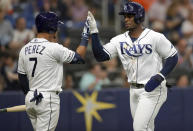 Tampa Bay Rays' Yandy Diaz, right, is congratulated by Michael Perez after scoring on a double by Kevin Kiermaier during the fifth inning of a baseball game against the Houston Astros, Saturday, March 30, 2019, in St. Petersburg, Fla. (AP Photo/Mike Carlson)