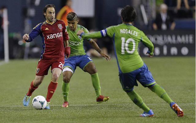 Real Salt Lake's Ned Grabavoy, left, drives against the defense of Seattle Sounders' DeAndre Yedlin, center, and Mauro Rosales (10) in the first half of an MLS soccer match, Friday, Sept. 13, 2013, in Seattle. (AP Photo/Ted S. Warren)