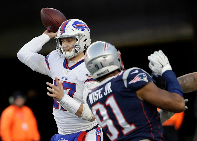 Buffalo Bills quarterback Josh Allen, left, passes under pressure from New England Patriots defensive end Deatrich Wise during the second half of an NFL football game, Sunday, Dec. 23, 2018, in Foxborough, Mass. (AP Photo/Steven Senne)