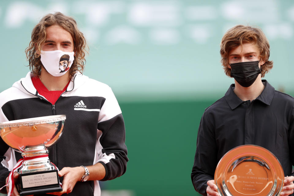 Stefanos Tsitsipas of Greece, left, poses with the trophy after defeating Andrey Rublev of Russia in the Monte Carlo Tennis Masters tournament finals in Monaco, Sunday, April 18, 2021. (AP Photo/Jean-Francois Badias)