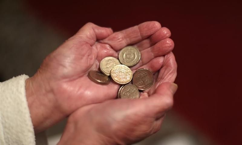 A pair of hands holding £1 coins