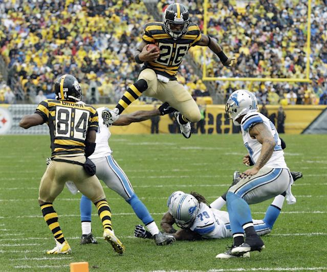 Pittsburgh Steelers running back Le'Veon Bell (26) leaps for more yardage as he tries to evade Detroit Lions strong safety Glover Quin (27) and the defense in the first half of an NFL football game in Pittsburgh, Sunday, Nov. 17, 2013. (AP Photo/Gene J. Puskar)