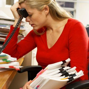 Stressed-businesswoman-holding-phone-to-head_web