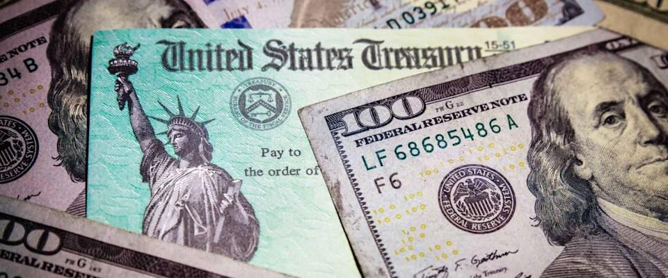 WASHINGTON DC - APRIL 2, 2020: United States Treasury check with US currency. Illustrates pandemic stimulus check payment.
