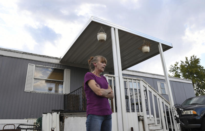 ADVANCE ON THURSDAY, SEPT. 12 FOR USE ANY TIME AFTER 3:01 A.M. SUNDAY SEPT 15 - In this Aug. 30th 2019 photo shows Karla Lyons, outside her mobile home at the Lamplighter Village in Federal Heights, Colo. Lyons' waitressing wages are eaten up by a constant stream of home and yard repairs ordered by her park manager, including removal of a giant maple tree that fell on her patio roof and crushed it. She would move if she could afford it. (Kathryn Scott/The Colorado Sun)