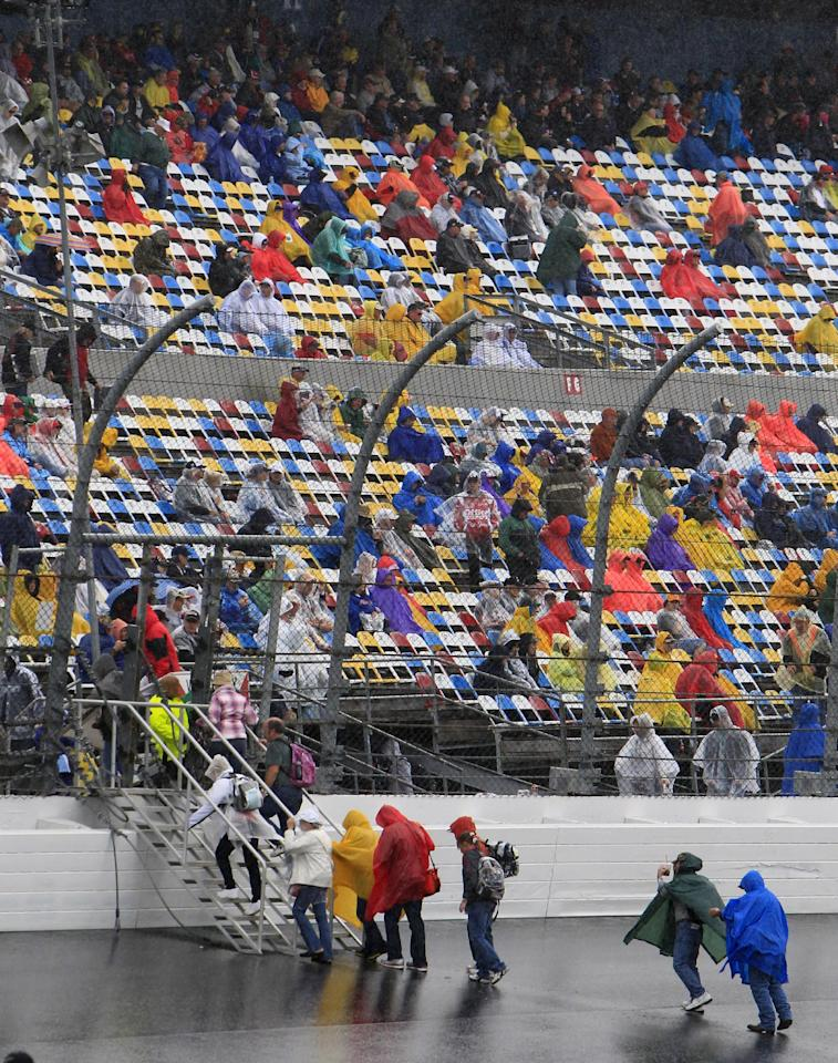 Fans make their way to the grandstands during a rain delay before the NASCAR Daytona 500 auto race at Daytona International Speedway in Daytona Beach, Fla., Sunday, Feb. 26, 2012. (AP Photo/John Raoux)