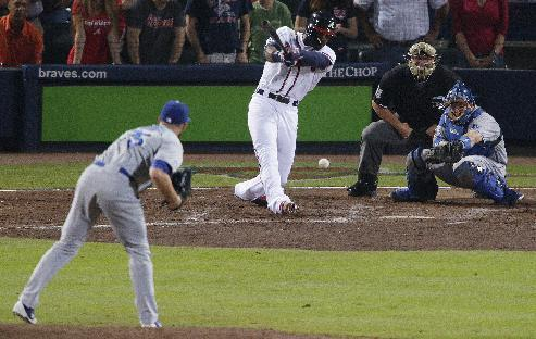 Atlanta Braves' Jason Heyward, center, hits a two-RBI single, scoring teammates Justin Upton and Chris Johnson, in the seventh inning of Game 2 of the National League division series against the Los Angeles Dodgers, Friday, Oct. 4, 2013, in Atlanta. (AP Photo/Dave Martin)