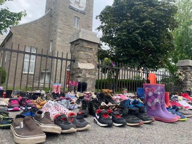 Children's shoes are placed in front of a church in Kahnawake, Que., after the remains of an estimated 215 children were found in unmarked graves near the site of a former residential school in Kamloops, B.C., in May. (Chloe Ranaldi/CBC - image credit)