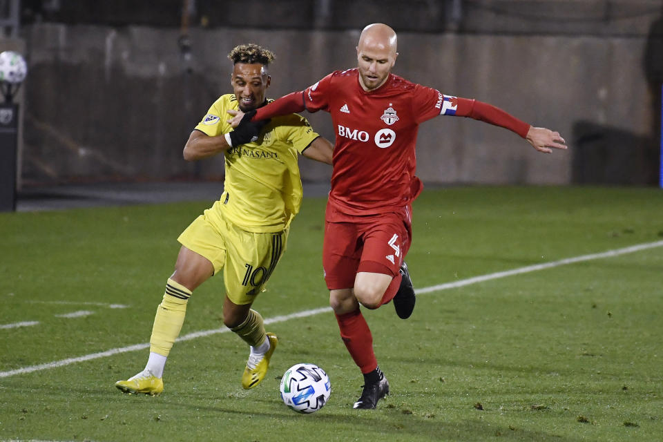 Nashville SC's Hany Mukhtar, left, and Toronto FC's Michael Bradley vie for control of the ball during the first half of an MLS soccer playoff match Tuesday, Nov. 24, 2020, in East Hartford, Conn. (AP Photo/Jessica Hill)
