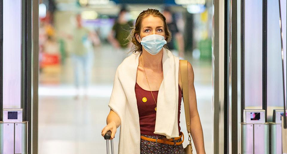 A woman wearing a face mask pushes a suitcase.