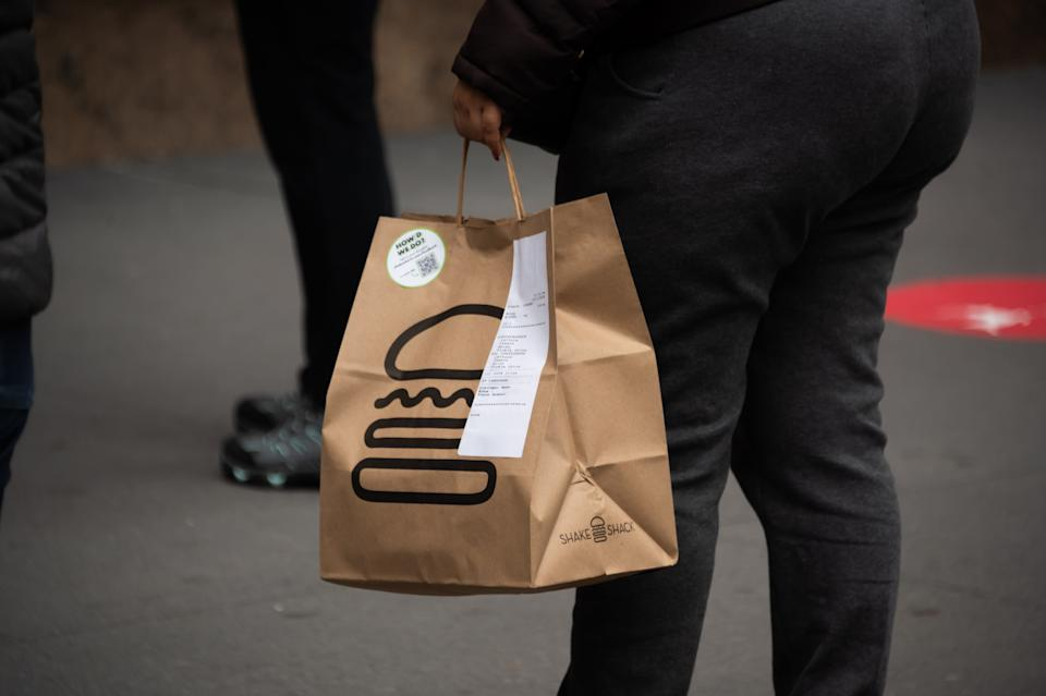NEW YORK, NEW YORK - DECEMBER 02: A person carries a Shake Shack takeout bag in Herald Square as the city continues the re-opening efforts following restrictions imposed to slow the spread of coronavirus on December 02, 2020 in New York City. The pandemic has caused long-term repercussions throughout the tourism and entertainment industries, including temporary and permanent closures of historic and iconic venues, costing the city and businesses billions in revenue. (Photo by Noam Galai/Getty Images)