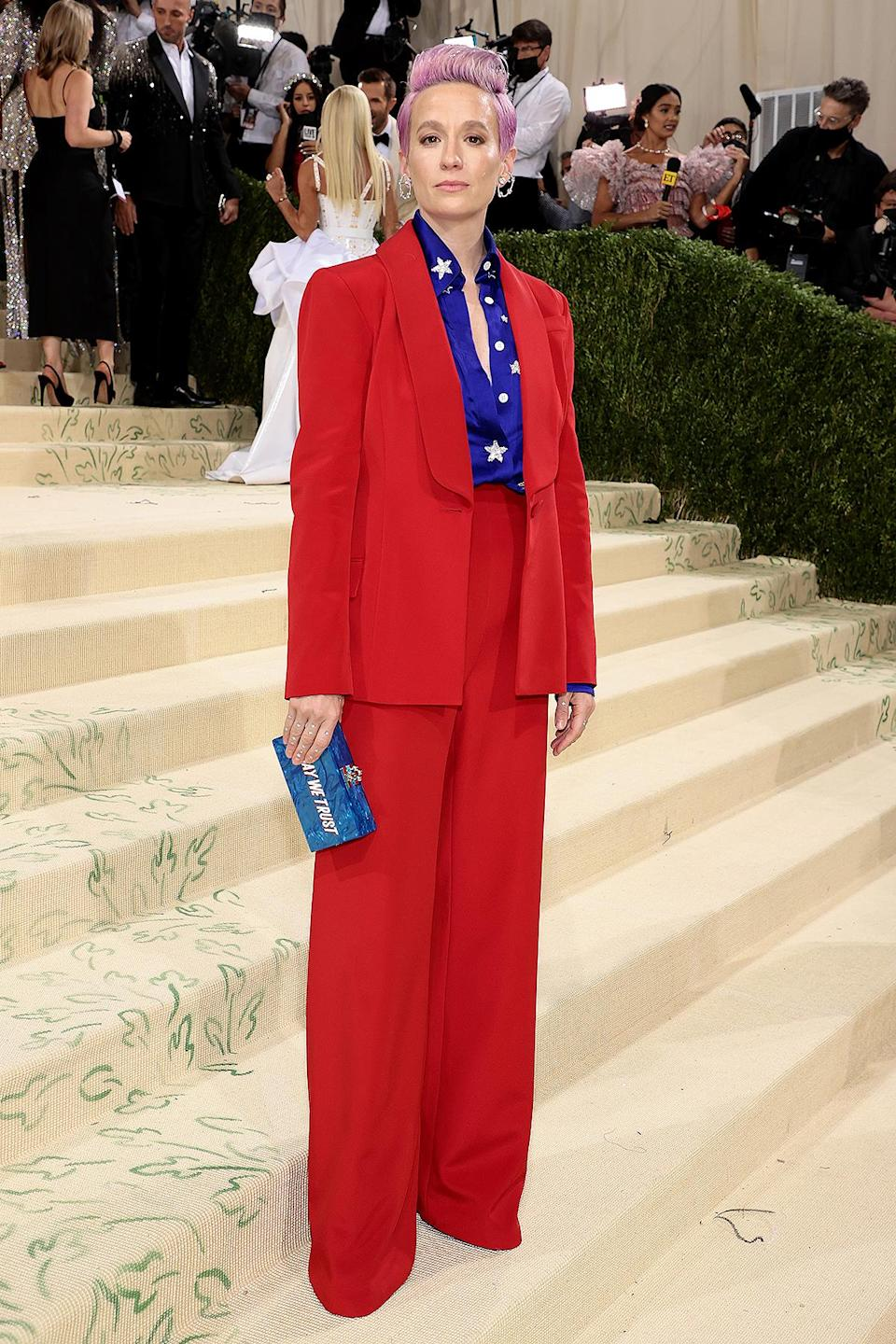"""<p>Carrying an Edie Parker clutch emblazoned with the words """"In Gay We Trust,"""" soccer superstar Rapinoe wore a custom red suit by Sergio Hudson with a blue, star-covered shirt.</p>"""