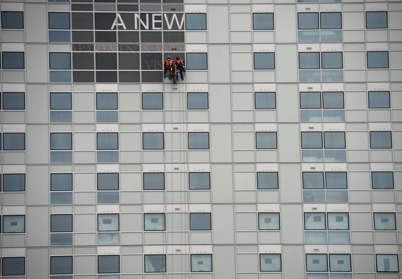 Workers put up a sign on a newly constructed office and apartment building in the heart of London