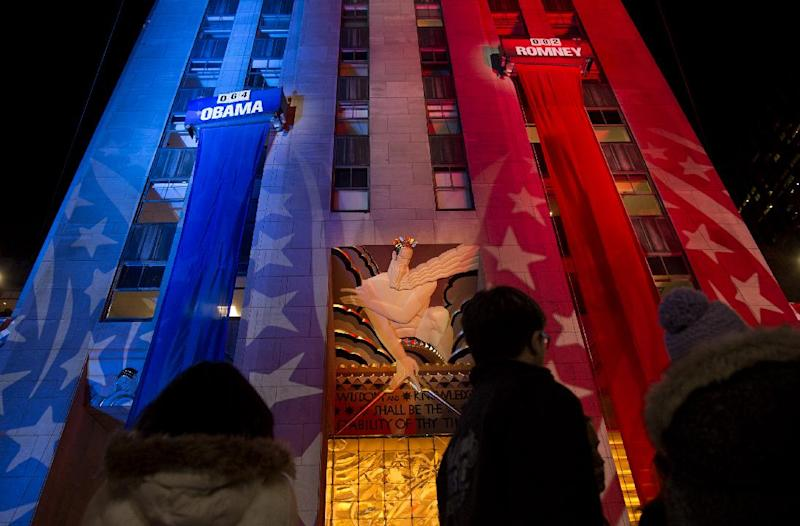 People watch early election results displayed on a utility lift suspended from the front of the GE Building at Rockefeller Center New York, Tuesday, Nov. 6, 2012. (AP Photo/Craig Ruttle)