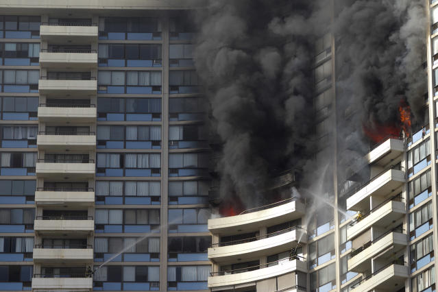 <p>Firefighters on several balconies spray water upwards while trying to contain a fire at the Marco Polo apartment complex, Friday, July 14, 2017, in Honolulu, Hawaii. (Photo: Marco Garcia/AP) </p>