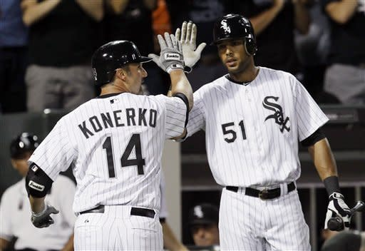 Chicago White Sox's Paul Konerko (14) looks back at left field as he celebrates his home run off Minnesota Twins starting pitcher Cole De Vries with Alex Rios during the fifth inning of a baseball game, Tuesday, July 24, 2012, in Chicago. (AP Photo/Charles Rex Arbogast)