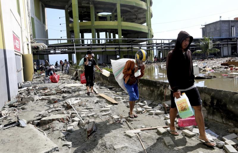 In this Sunday, Sept. 30, 2018, file photo, people carry away items from a shopping mall badly damaged by a massive earthquake and tsunami in Palu, Central Sulawesi, Indonesia. (AP Photo/Tatan Syuflana, File)