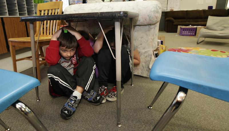 "Jacob Foster, 7, a student at Twin Lakes Elementary School in Federal Way, Wash., takes shelter under a table with other students as they take part in an earthquake drill, Thursday, Oct. 18, 2012. Millions of people took part in the ""Great Shakeout"" earthquake drill across the country and elsewhere Thursday to practice and prepare for the possibility of real quakes in the future. (AP Photo/Ted S. Warren)"