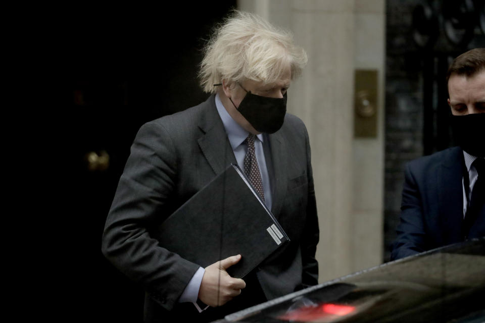 British Prime Minister Boris Johnson leaves 10 Downing Street to go to the Houses of Parliament, in London, Monday, Feb. 22, 2021. Johnson on Monday is expected to announce a plan to ease coronavirus restrictions in increments, starting by reopening schools in England on March 8. (AP Photo/Matt Dunham)