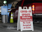 """A sign posted reads """"Covid-19 Update. Effective Inmediately. No Cash Accepted at Exits,"""" at a Los Angeles International Airport main parking lot in Los Angeles, Friday, Nov. 13, 2020. California has become the second state to record 1 million confirmed coronavirus infections. The governors of California, Oregon and Washington issued travel advisories Friday, Nov. 13, 2020, urging people entering their states or returning from outside the states to self-quarantine to slow the spread of the coronavirus, California Gov. Gavin Newsom's office said. The advisories urge people to avoid non-essential out-of-state travel, ask people to self-quarantine for 14 days after arriving from another state or country and encourage residents to stay local, a statement said. (AP Photo/Damian Dovarganes)"""