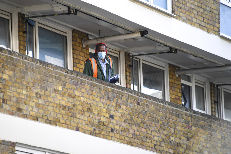 A postman is seen at work in East London as he wear a surgical mask, due to the Coronavirus outbreak, in London, Saturday, March 28, 2020. The public have been asked to self isolate, keeping distant from others to limit the spread of the contagious COVID-19 coronavirus. The new coronavirus causes mild or moderate symptoms for most people, but for some, especially older adults and people with existing health problems, it can cause more severe illness or death. (AP Photo/Alberto Pezzali)