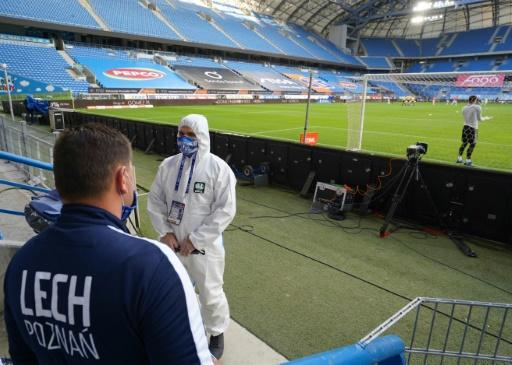 A man in a protective suit stands pitchside in Poznan before the restart of the Polish season last weekend following the coronavirus shutdown