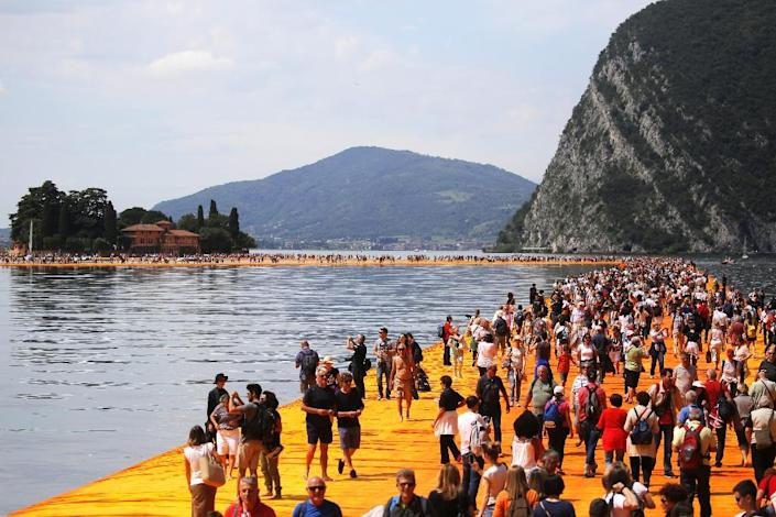 """Visitors from around the world have flocked to try """"The Floating Piers,"""" many of them going barefoot to get an idea of what it feels like to """"walk on water"""" (AFP Photo/Marco Bertorello)"""
