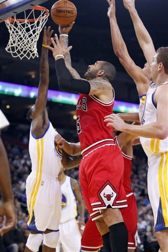 Chicago Bulls' Carlos Boozer (5) drives to the basket past Golden State Warriors' Monta Ellis (8) during the first half of an NBA basketball game Monday, Dec. 26, 2011, in Oakland, Calif. (AP Photo/Tony Avelar)