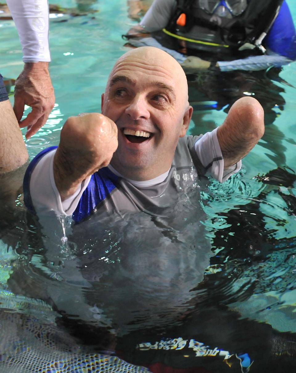 French Philippe Croizon, 44, celebrates on January 10, 2013 after becoming the first quadruple amputee to dive at a depth of 33 meters in the deepest swiming pool in the world in Brussels. He used flippers attached to prosthetic limbs to dive with a group of 15 Belgian divers to the bottom of the pool to set a new world record for an amputee. Croizon had all four limbs amputated in 1994 after being struck by an electric shock of more than 20,000 volts as he tried to remove a TV antenna from a roof. He has swum across the English Channel and all five intercontinental channels. AFP PHOTO GEORGES GOBETGEORGES GOBET/AFP/Getty Images