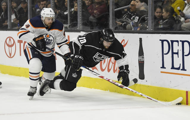 Los Angeles Kings center Tobias Rieder, of Germany, falls as he battles for the puck with Edmonton Oilers defenseman Kris Russell during the second period of an NHL hockey game Saturday, Feb. 24, 2018, in Los Angeles. (AP Photo/Mark J. Terrill)
