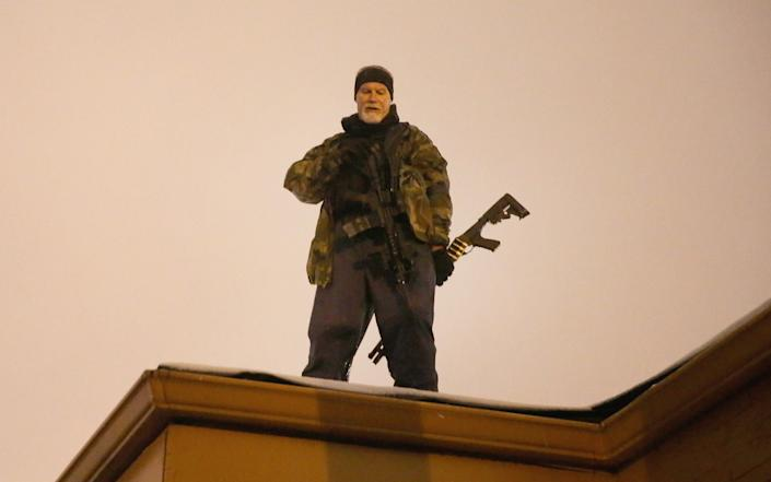John Karriman. a volunteer from Oath Keepers, stands guard on the rooftop of a business in Ferguson, Mo., Nov. 26, 2014. (Scott Olson/Getty Images)