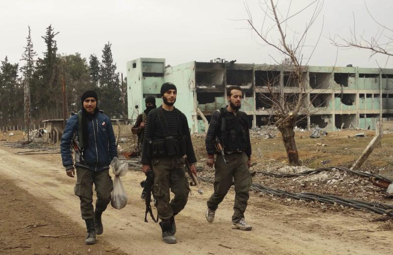 Free Syrian Army fighters walk with their weapons at the Tameko pharmaceutical factory, after the FSA claimed to have taken control of the factory, in eastern al-Ghouta, near Damascus January 14, 2014. REUTERS/Yaseen Abelall (SYRIA - Tags: POLITICS CIVIL UNREST CONFLICT)