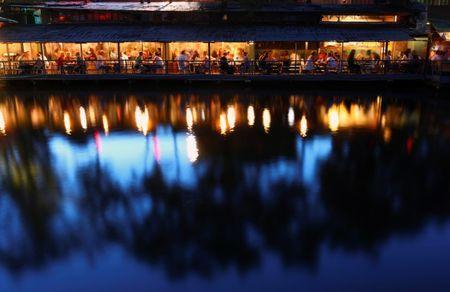 People sit in bars on the Flutgraben canal in Berlin, Germany, August 25, 2016. The area around the canal Flutgraben has blossomed into a nightlife district. REUTERS/Hannibal Hanschke
